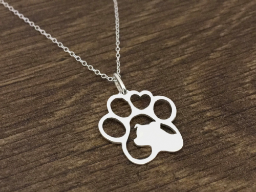 staffordshire bull terrier  in a paw with a heart pendant